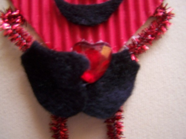Gluing red rhinestone in place.