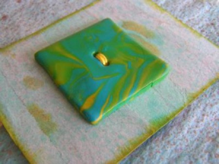Marbled green and gold clay button.