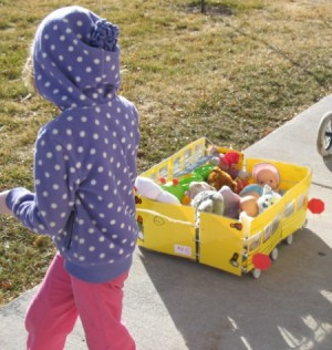 Child pulling school bus cart on sidewalk.