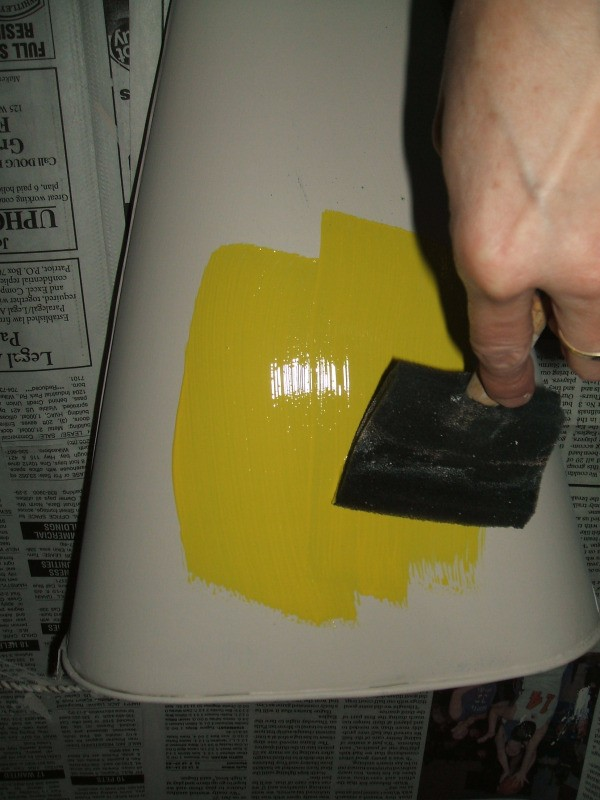 Painting the primed bucket yellow.
