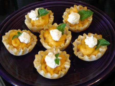 A plate of mini pumpkin tarts.