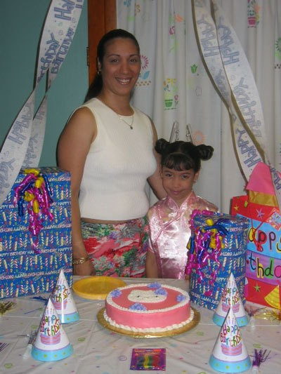A mom and daughter with a cake decorated with Hello Kitty.