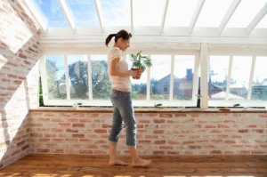 A woman stand in a room built using recycled windows.