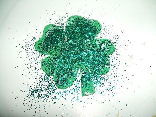 Gluing glitter to shamrock.