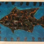 Scrap metal fish collage on wood.