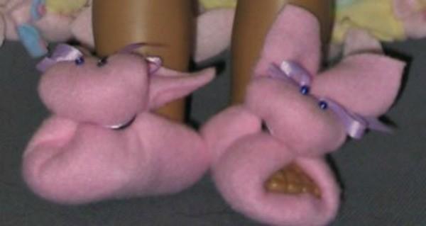 Pink fleece doll slippers shaped like bunnies.