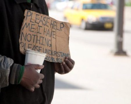 A homeless person holding up a sign