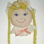 Hair accessory doll hanging on wall.