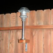 Attach Solar Lights to Your Fence - Solar light attached to a fence shown at night.
