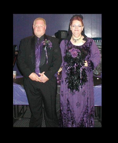 A couple dressed in black and purple formal wear, for a Goth wedding.