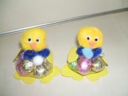 Two pom pom chicks holding Easter candy.