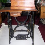 Wooden cabinet coffin style sewing machine.