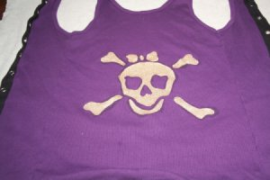 A pirate girl skull painted in gold on a purple tank top.