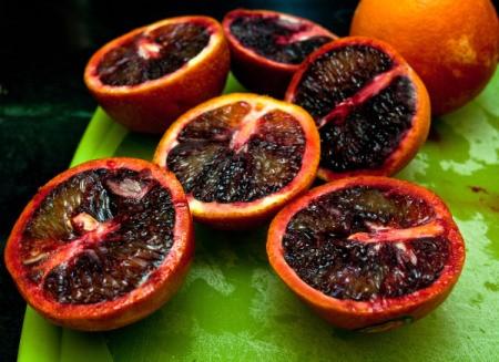 Several blood oranges cut in half.