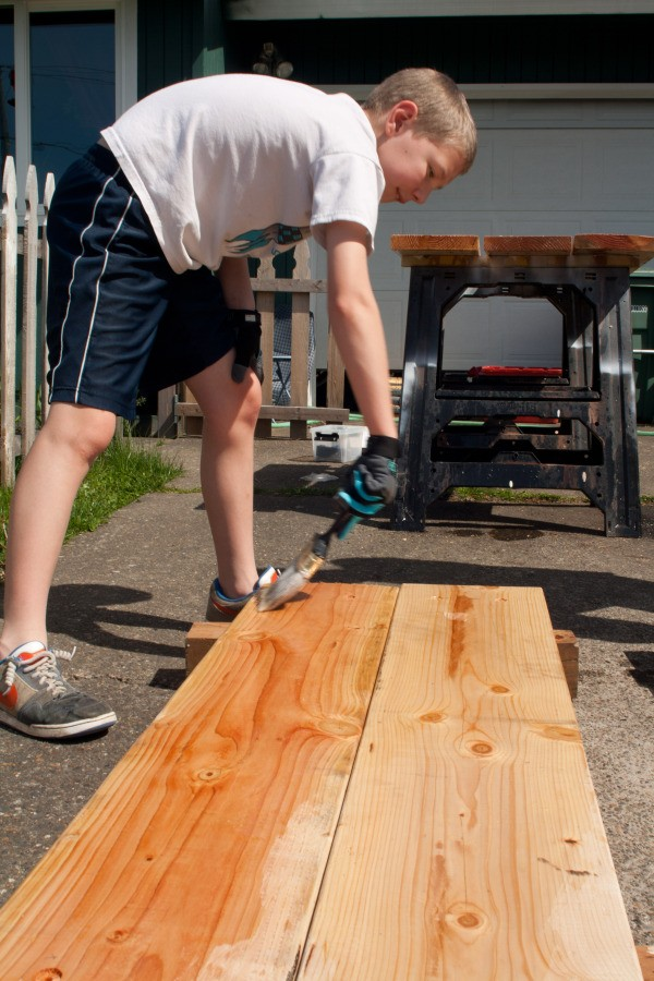 Square Foot Raised Garden Beds - Boy Helping Stain Panels