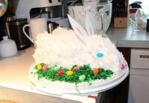 Easter Bunny Cake, fully decorated with green coconut grass and jelly beans.