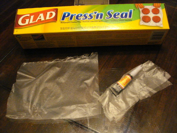 The Super glue tube is wrapped up inside a square of Press'N Seal plastic wrap.