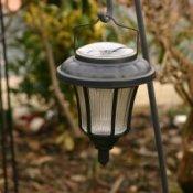 A solar patio light on a shepherd's hook.