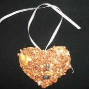 A bird biscuit made from birdseed in the shape of a heart.