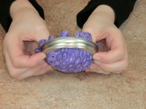 Fitting pin cushion parts into jar for fabric gluingring.