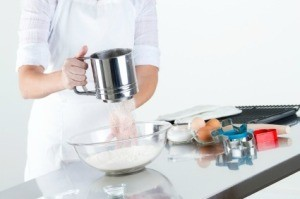 Woman Sifting Flour to Make Cookie Dough