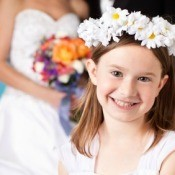 Flower Girl Smiling in Front of Bride and Groom