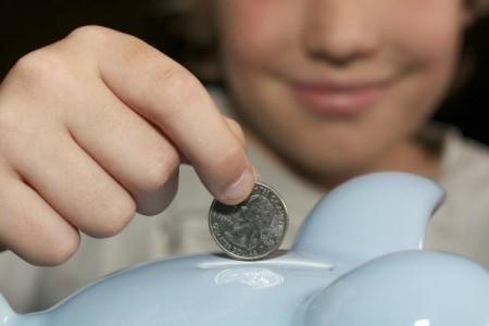 Boy Putting Quarter in Piggy Bank