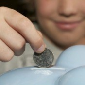Boy Putting Quarter in Piggy Bank