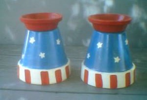 A pair of Fourth of July candle holders made from clay pots.