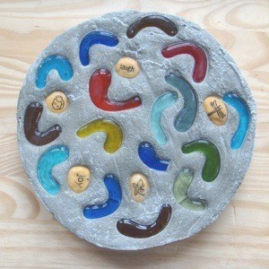 A homemade stepping stone with glass pieces and rocks placed in the cement.