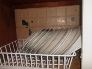 Dish drainer in cupboard.