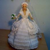 Doll wearing a crochet dress.