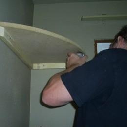 Man putting in Corner Shelves