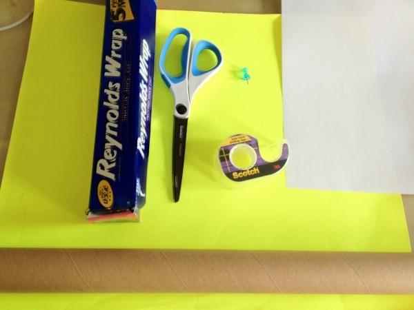Cardboard tube, aluminum foil, scissors, tape, push pin, and paper.