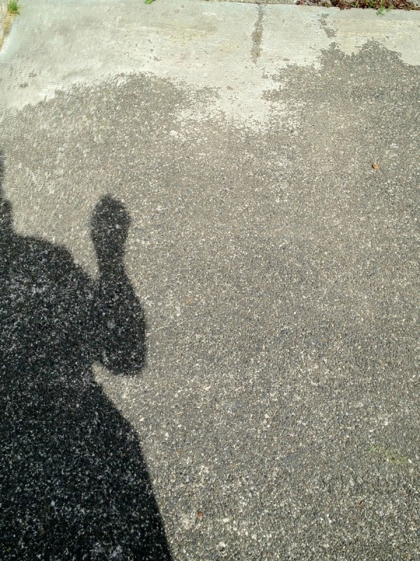 Shadow of man holding pinhole viewer aligned with sun.