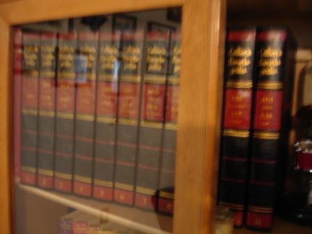 Encyclopedias on bookshelves.