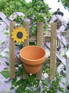 A decoration for you garden that looks like a picket fence with a clay pot on it.