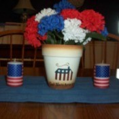 Flag decorated flower pot with red, white, and blue flowers.
