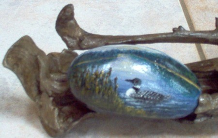 A close up of a painted rock placed in a piece of driftwood.