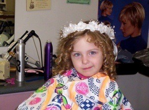 Child getting ready for wedding at beauty shop.