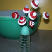 Red and white button flowers in salt shaker.