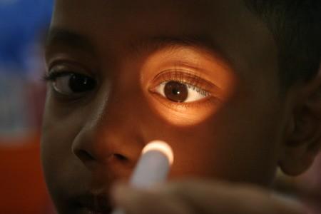 Examining a child's eyes.