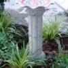 White bird bath in garden.