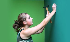 Girl Hammering Nail into Wall