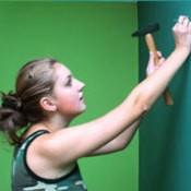 Girl Hammering Nail into Wall