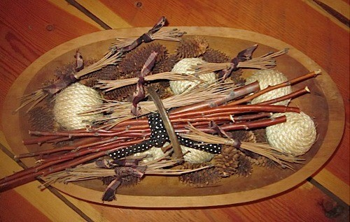 Pine needle bundles in wooden bowl with other nature decorations, such as pine cones, etc.