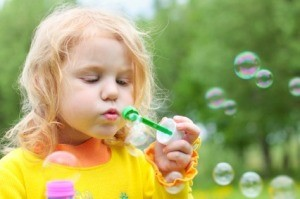 A little girl blowing bubbles.