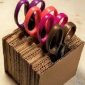 A holder made out of recycled cardboard for scissors or paper edgers.