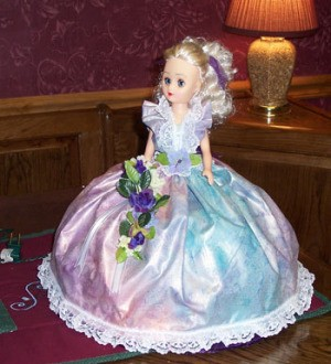Front view of doll in pink dress.