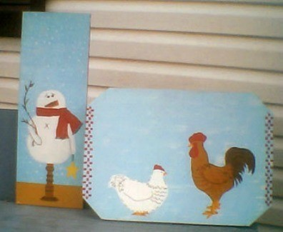 Painted boards with snowman and chickens.